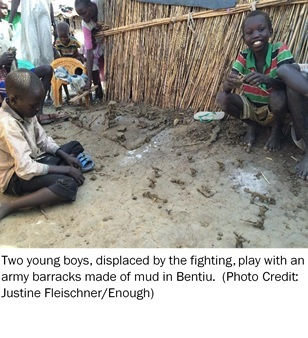 Two young boys displaced by the fighting play with an army barracks made of mud in Bentiu