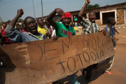 Protestors carry a sign reading 'Resign Djotodia,' in CAR.