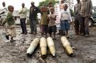 Congolese citizens look at tank shells after M23 rebel takeover in Goma.