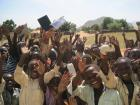 Kids at the Djabal refugee camp wave as school lets out for the day.
